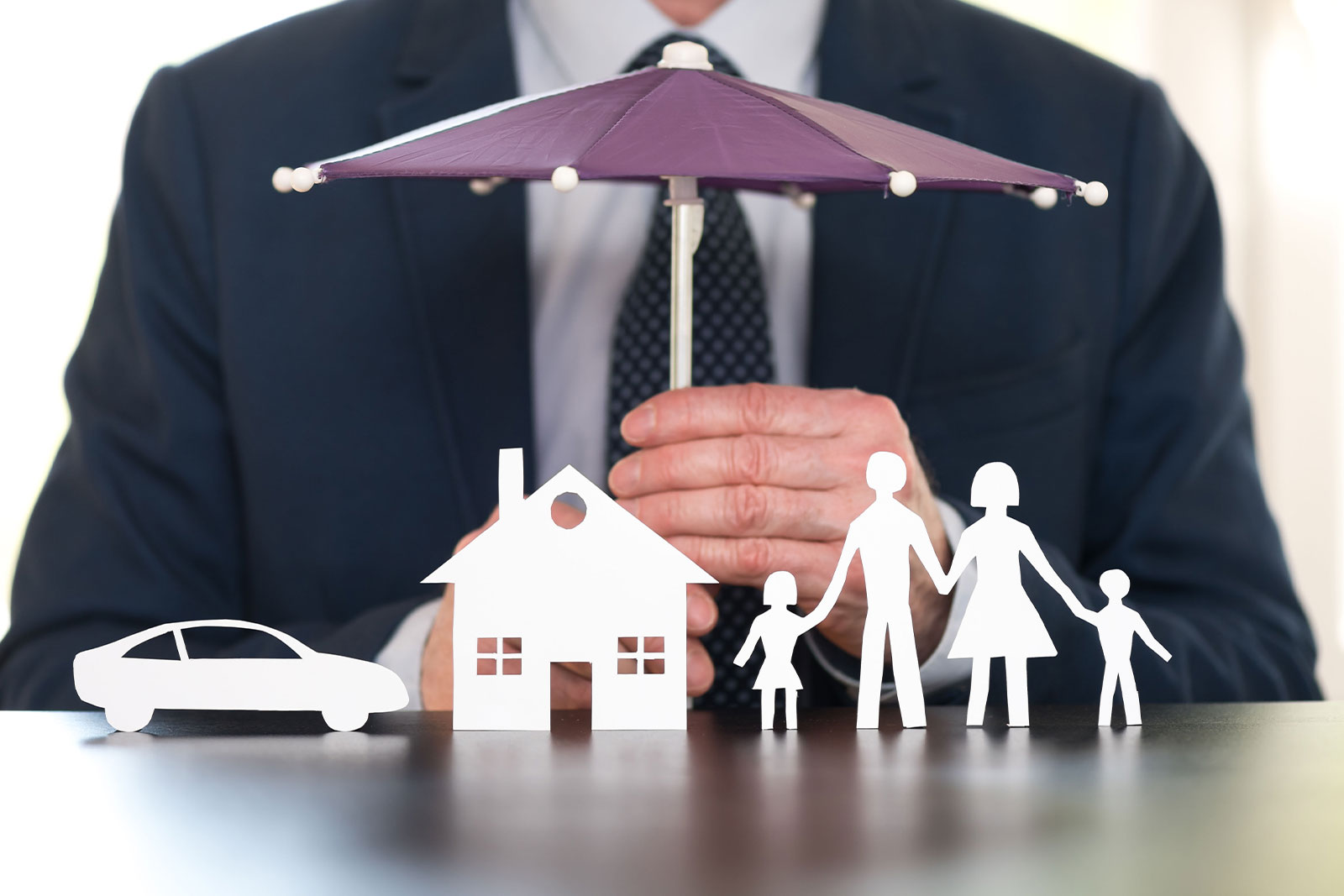 Image of man holding small umbrella over paper cut out a house, care, and family